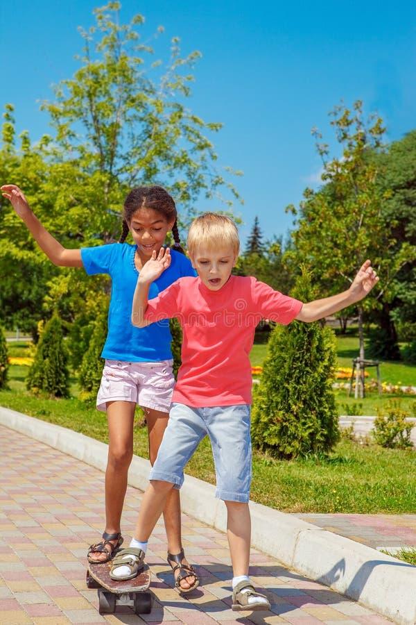 男孩和女孩同一个滑板的 库存图片