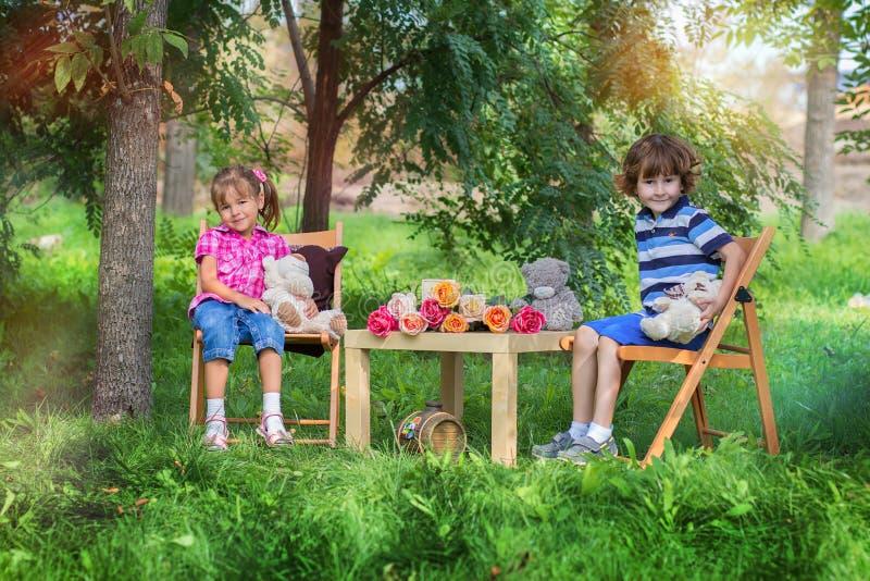 男孩和女孩在一张小桌上坐在树中的街道 免版税库存照片