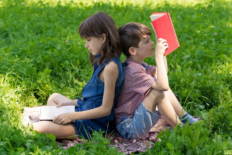 男孩和女孩在公园和阅读书紧接坐草坪 库存图片
