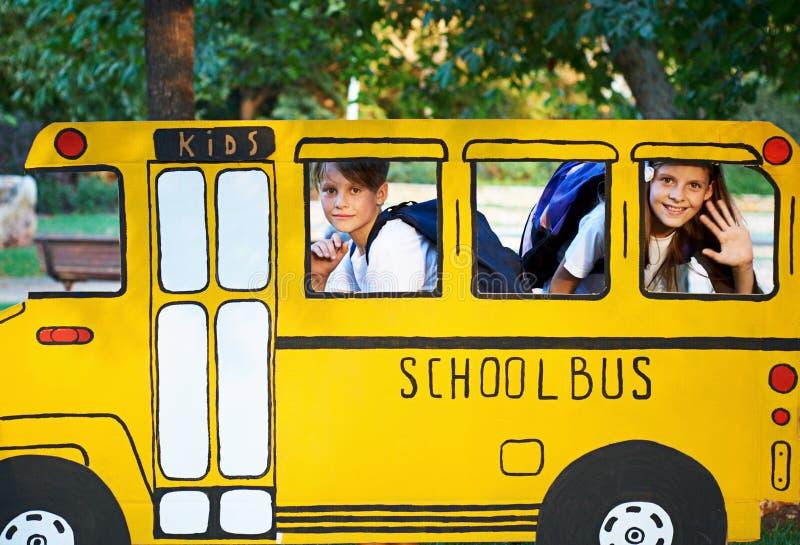 男孩和女孩在小校车上 库存图片