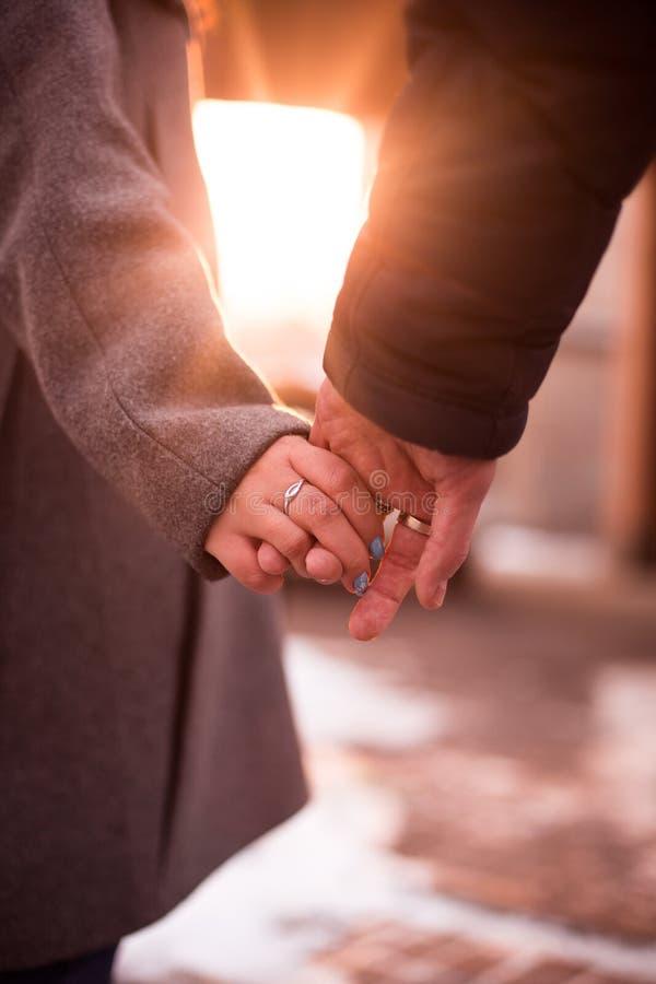 男孩和女孩在日落美丽的太阳的举行手 免版税图库摄影