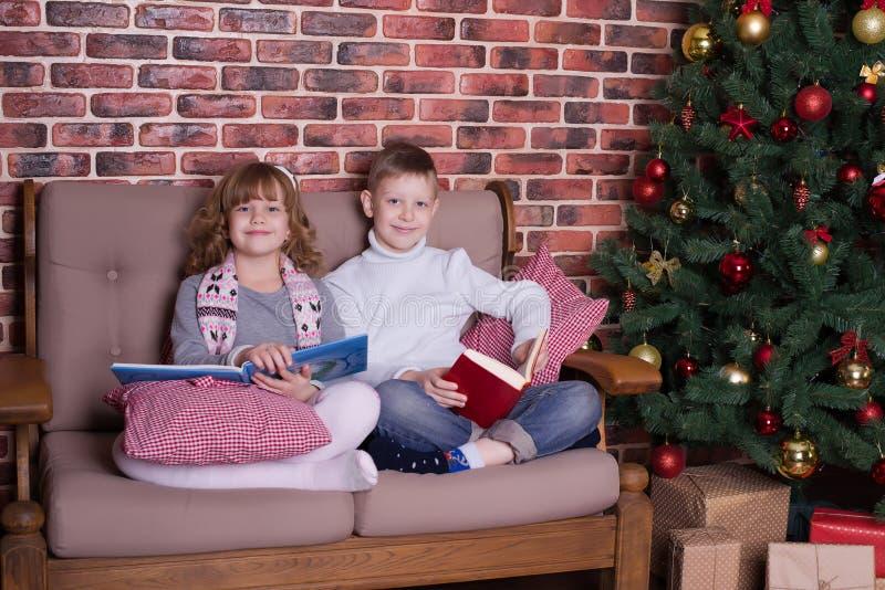 男孩和女孩在沙发的阅读书 免版税图库摄影