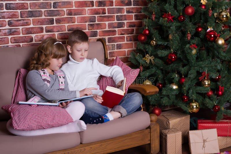 男孩和女孩在沙发的阅读书 库存照片