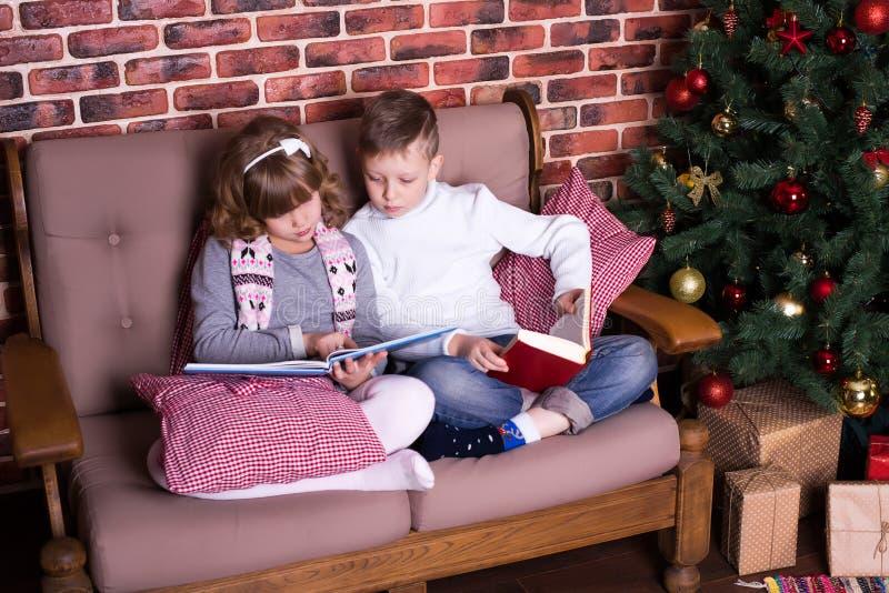 男孩和女孩在沙发的阅读书 免版税库存图片