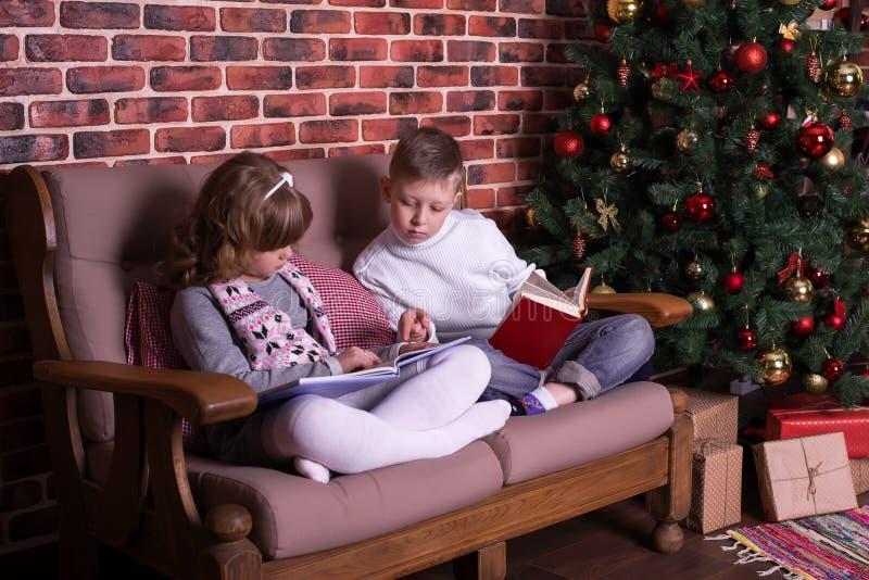 男孩和女孩在沙发的阅读书 库存图片