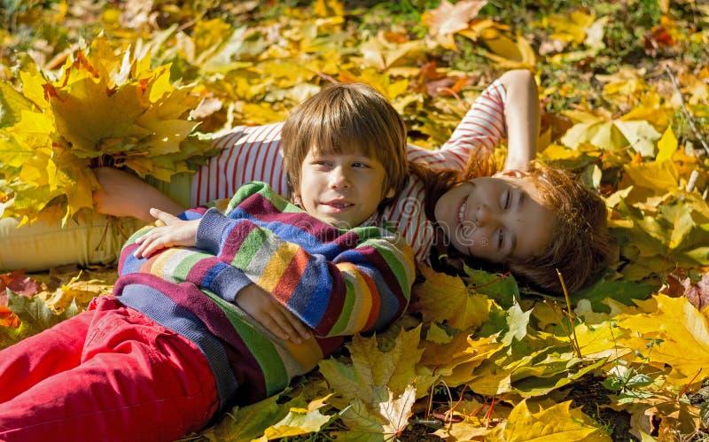 男孩和女孩在黄色叶子说谎在公园 免版税图库摄影