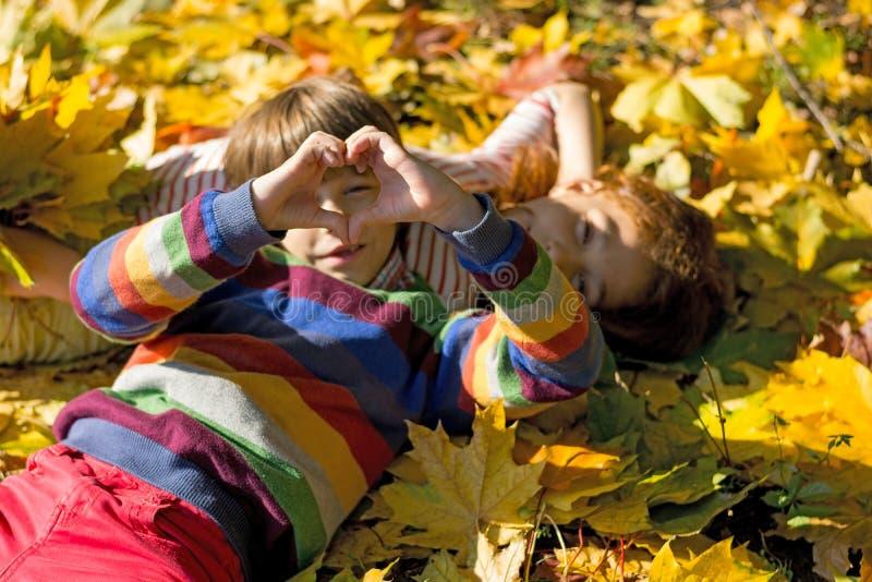 男孩和女孩在黄色叶子说谎在秋天公园 免版税图库摄影