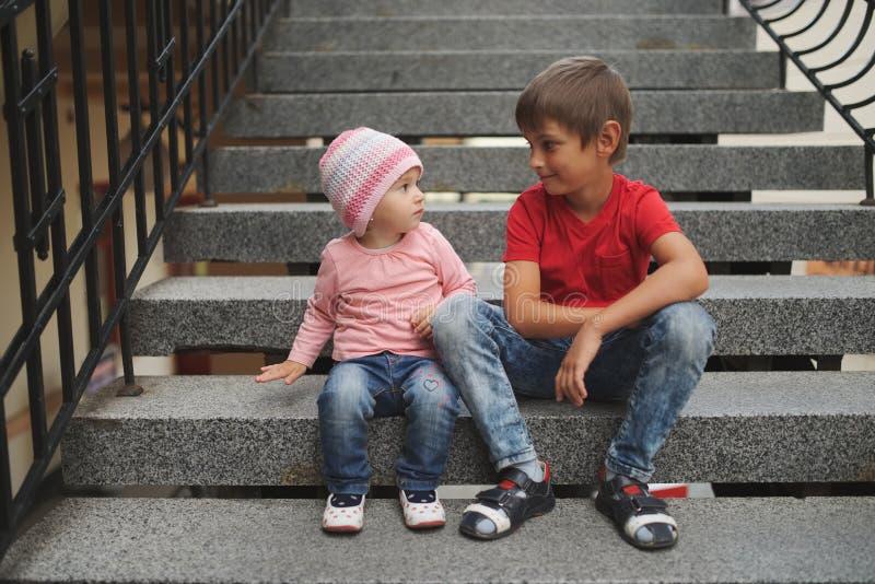 男孩和女孩坐楼梯 免版税库存照片