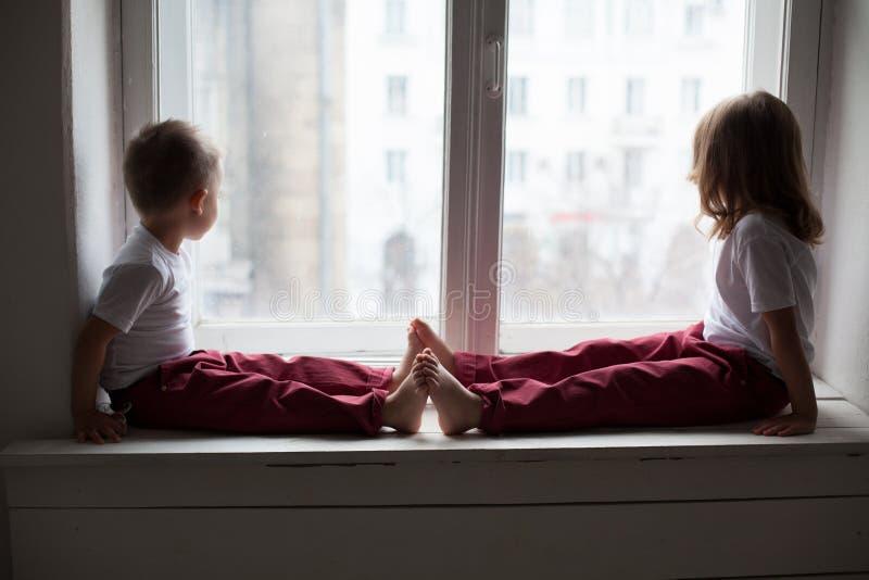男孩和女孩坐看窗口的窗台 免版税库存图片