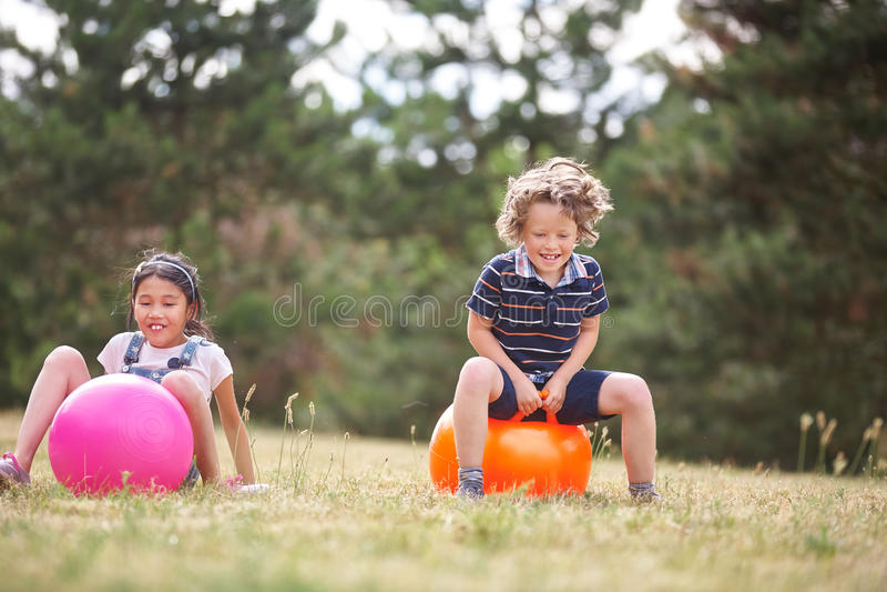 男孩和女孩坐spacehooper 免版税库存图片