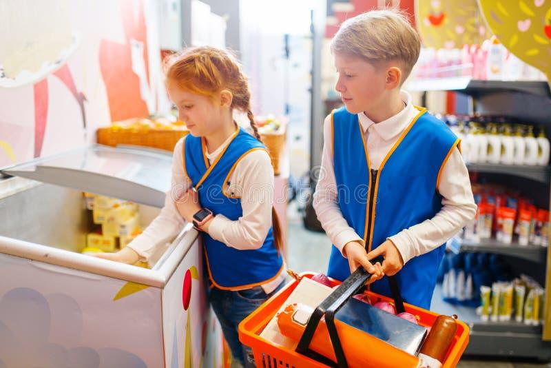 男孩和女孩扮演卖主,游戏室的制服的 免版税图库摄影