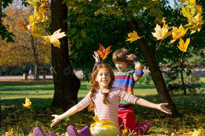 男孩和女孩投掷黄色叶子在秋天 免版税库存图片