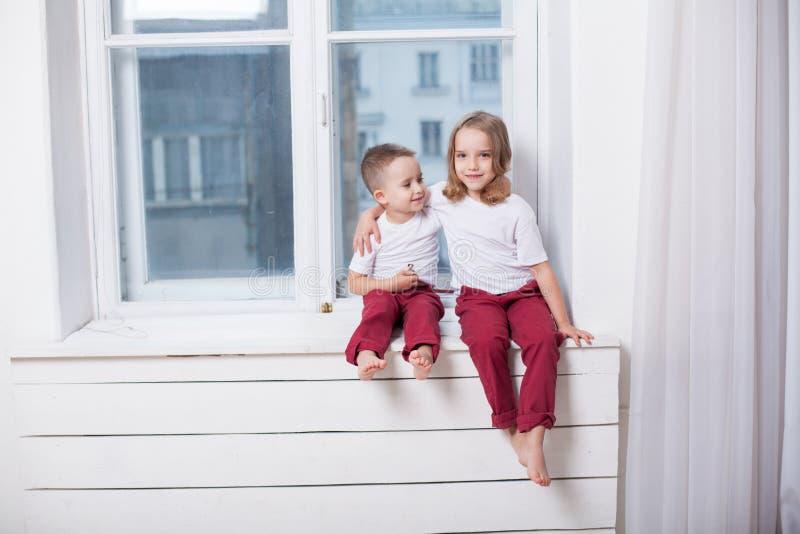 男孩和女孩是兄弟,并且姐妹坐窗台在窗口 库存照片