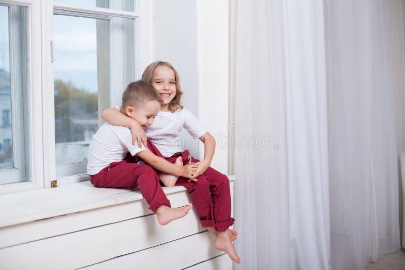 男孩和女孩是兄弟,并且姐妹坐窗台在窗口 免版税库存照片