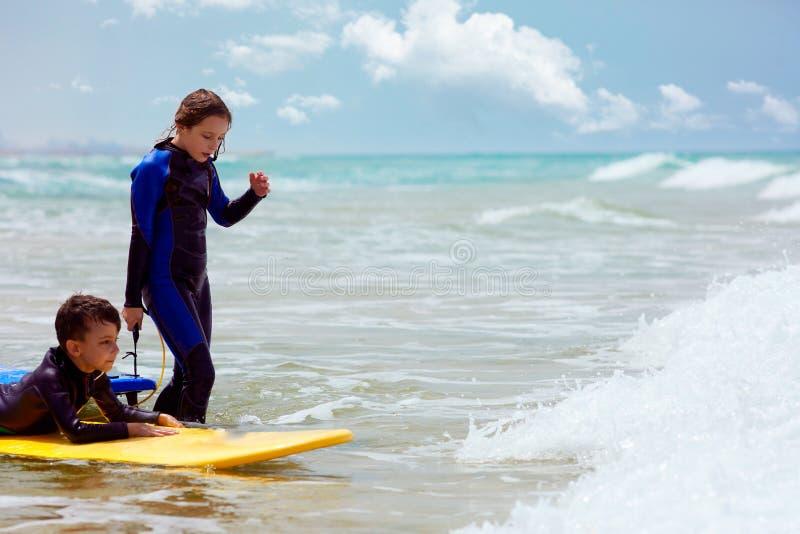 男孩和女孩有冲浪板的在挥动的海 免版税图库摄影