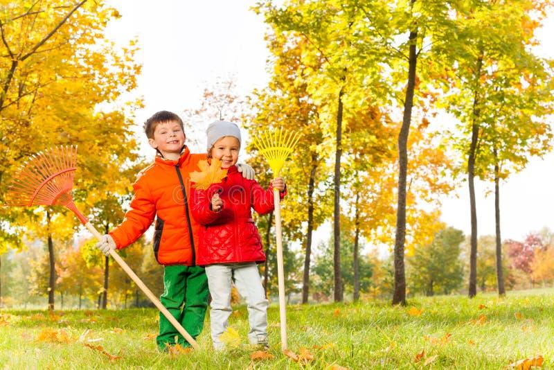 男孩和女孩有犁耙的在秋天公园站立 库存图片