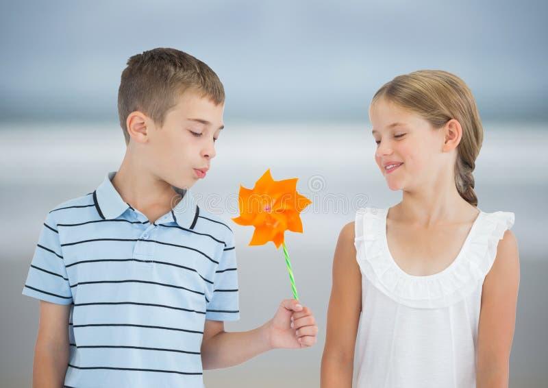 男孩和女孩有玩具风车的反对模糊的海滩 免版税库存图片