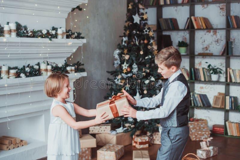 男孩和女孩由壁炉穿戴了典雅站立在一间明亮的屋子 圣诞树在背景中 概念新年度 库存照片