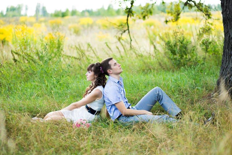 男孩和女孩的画象坐草 免版税库存图片
