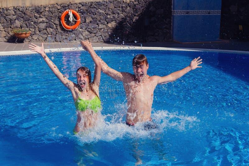 男孩和女孩获得乐趣在游泳池 免版税图库摄影