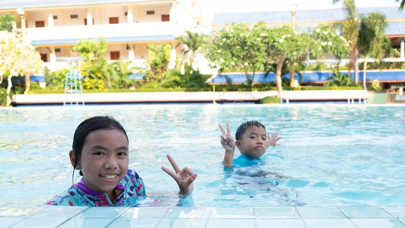 男孩和女孩获得使用的乐趣在水池 免版税库存图片