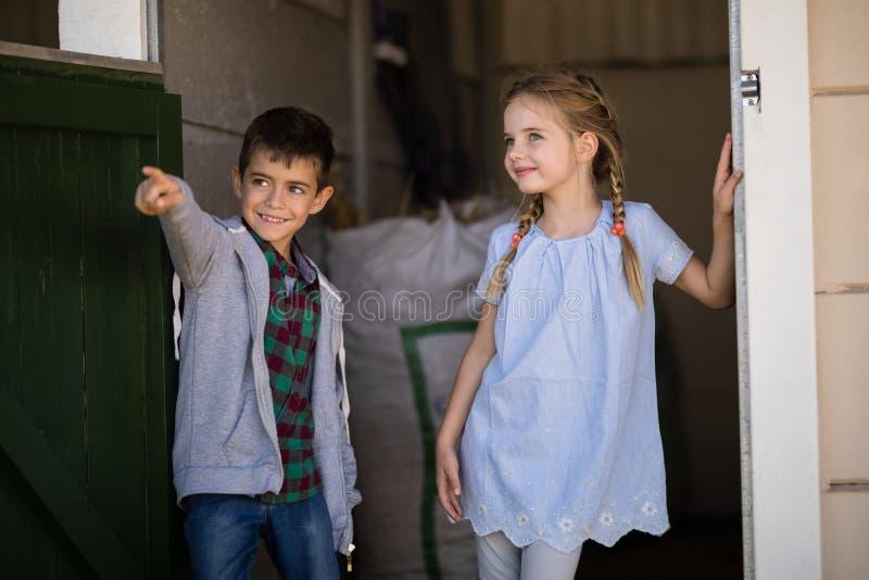 男孩和女孩谈话在彼此在槽枥 免版税图库摄影