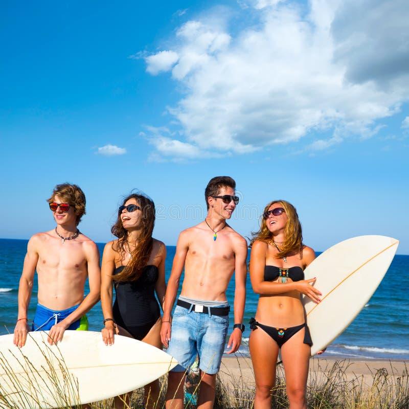 男孩和女孩青少年的冲浪者愉快微笑在海滩 免版税库存照片