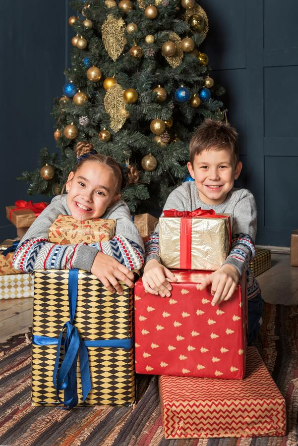 男孩和女孩,有姐妹的,微笑的兄弟姐妹兄弟在圣诞树附近坐愉快地拥抱礼物盒 免版税库存图片