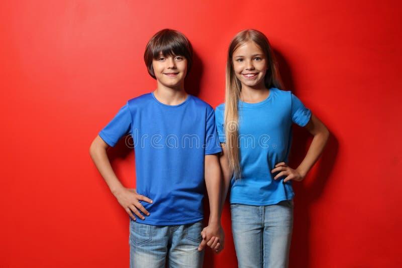 男孩和女孩T恤杉的在颜色背景 库存照片