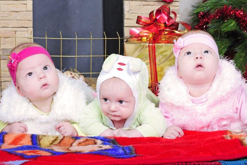 男孩和孪生女孩临近圣诞树 库存图片