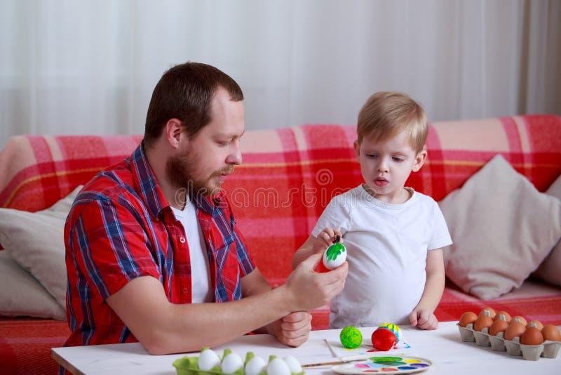 男孩和爸爸油漆鸡蛋 库存图片
