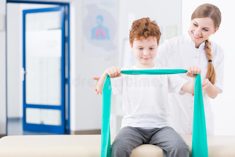 男孩和物理疗法在诊所 库存图片