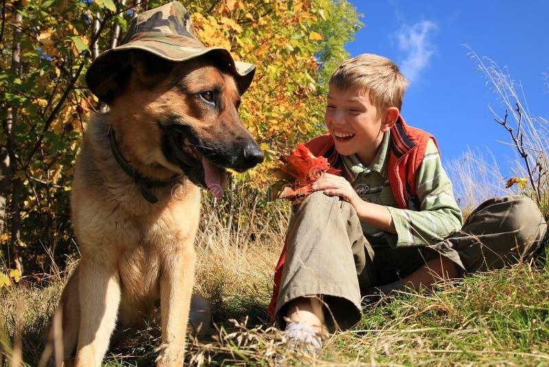 男孩和狗â晴朗的秋天 库存照片