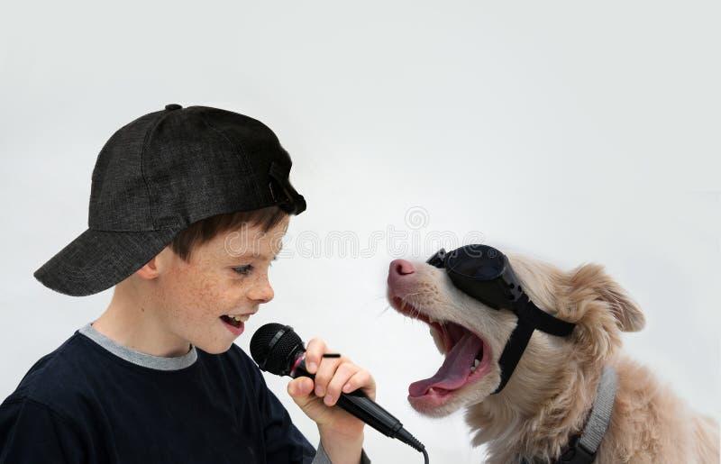 男孩和狗唱歌卡拉OK演唱 免版税库存照片