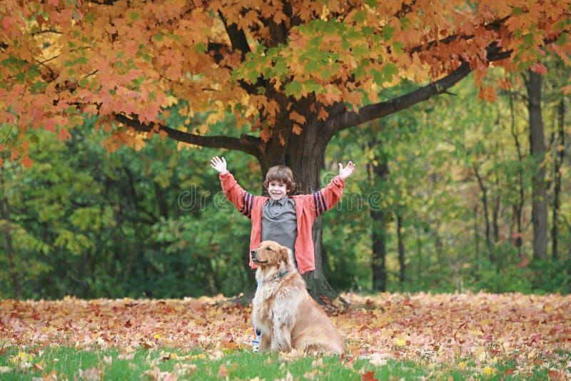 男孩和狗在秋天 免版税库存图片