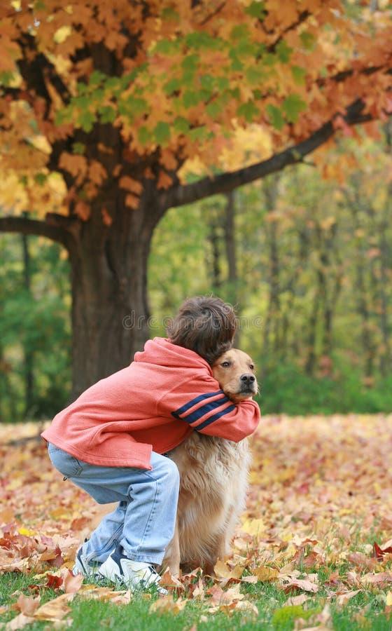 男孩和狗在秋天 免版税图库摄影