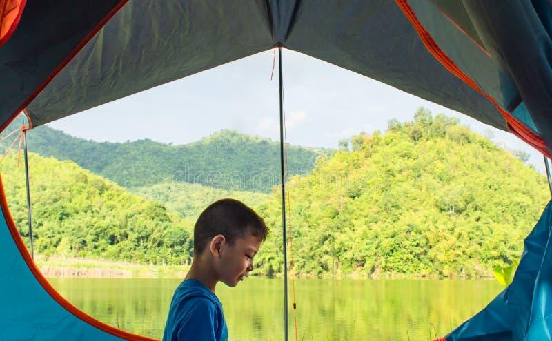 男孩和露宿帐篷的山背景的画象  库存照片