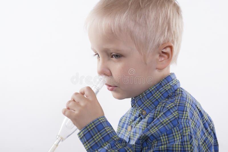 男孩和鼻吸气器 免版税库存照片