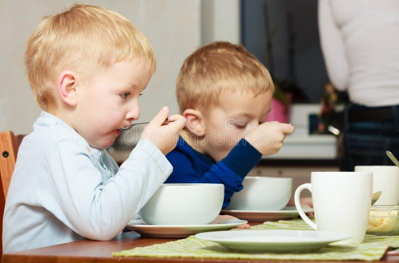 男孩哄骗吃玉米片早餐膳食的孩子在桌上 库存图片