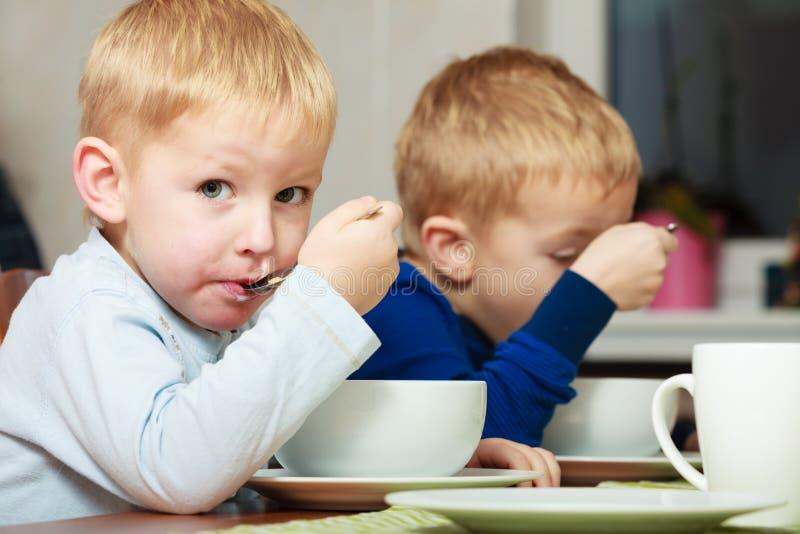 男孩哄骗吃玉米片早餐膳食的孩子在桌上 免版税库存照片