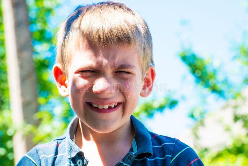 男孩哭泣泪花自在街道上的白天并且需要哀怜,特写镜头 图库摄影