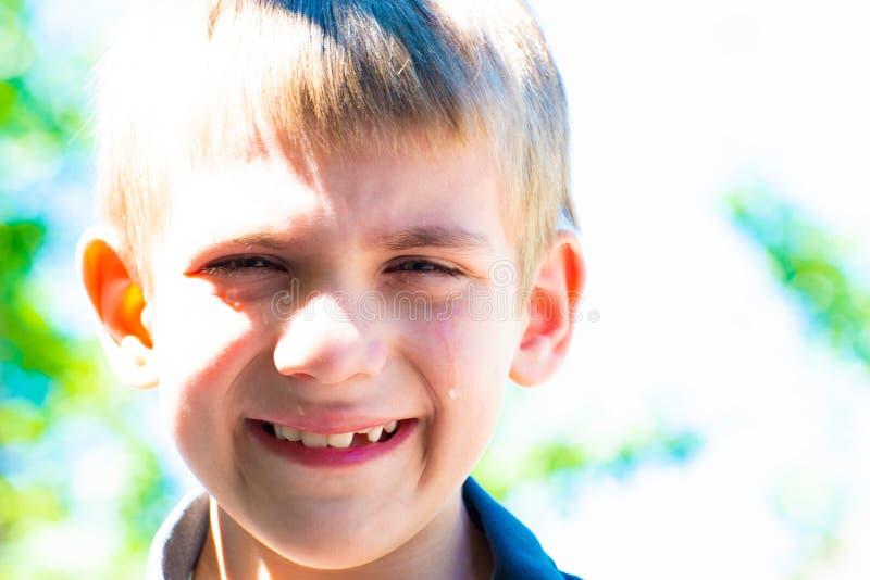 男孩哭泣泪花自在街道上的白天并且需要哀怜,特写镜头 免版税库存图片