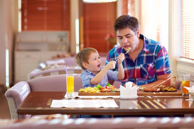 男孩哺养的父亲在餐馆 库存照片
