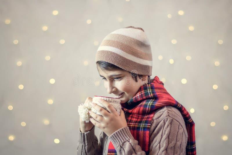 男孩喝从杯子的热巧克力 免版税库存图片