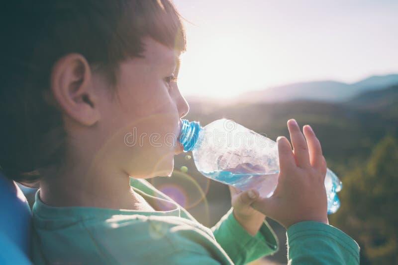 男孩喝从瓶的水 免版税库存照片