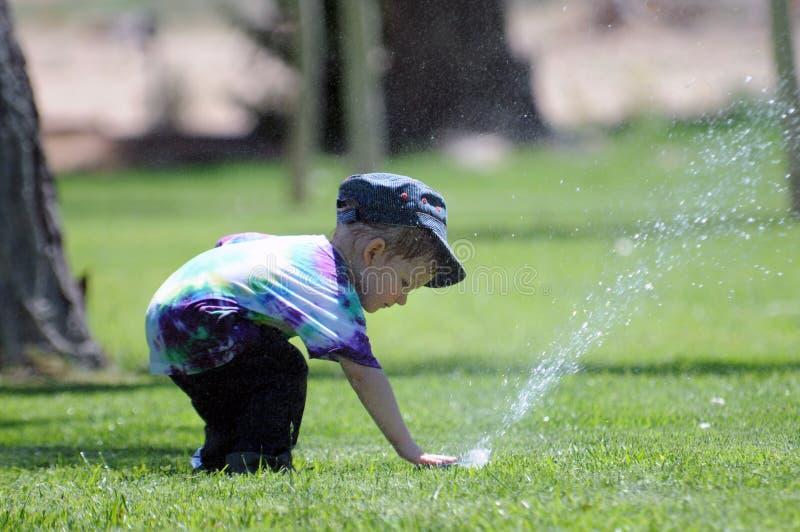 男孩喷水隆头水 免版税库存图片