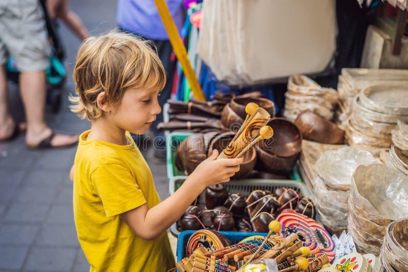 男孩在一个市场上在Ubud,巴厘岛 卖巴厘岛的纪念品和工艺品典型的纪念品店在著名Ubud市场上 库存照片