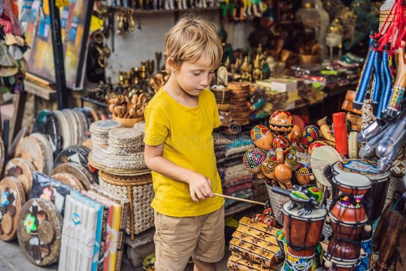 男孩在一个市场上在Ubud,巴厘岛 卖巴厘岛的纪念品和工艺品典型的纪念品店在著名Ubud市场上 免版税库存照片