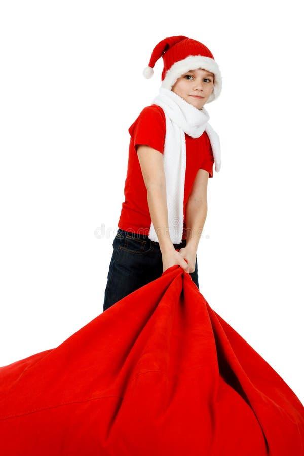 男孩在与圣诞节礼品袋子的圣诞老人帽子 免版税库存图片