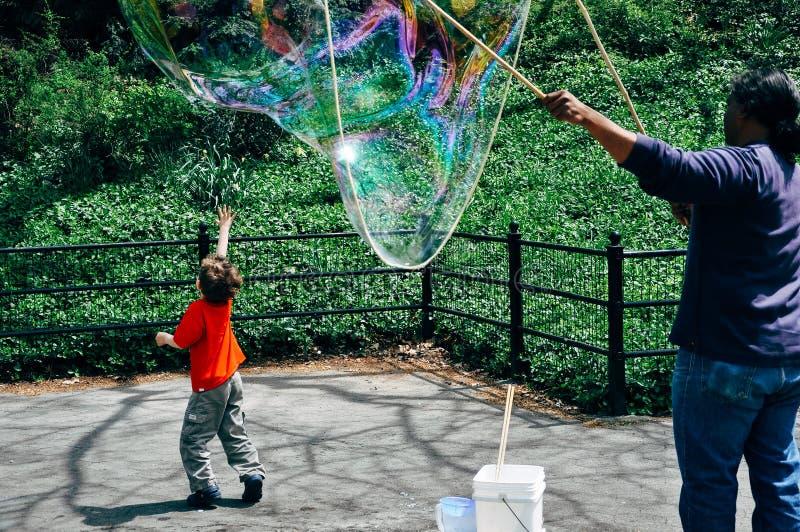 年轻男孩在中央公园追逐大气球 免版税库存照片